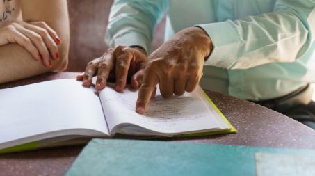 Une personne qui indiquent le texte dans un cahier à une autre